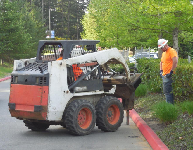 Bobcat drilling holes for a driven post rental fence.