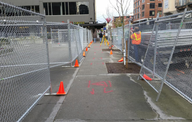 Setting up rental fencing for an urban construction site.